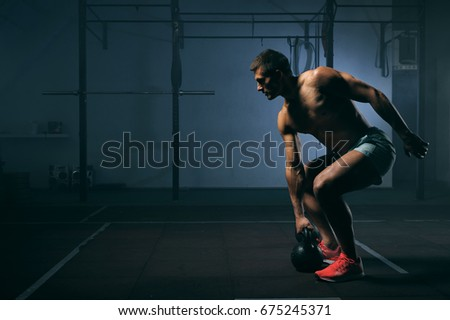 Young muscular man with naked torso working out in gym. Athletic male adult exercising with kettle bell. Fitness, sports concept. #675245371