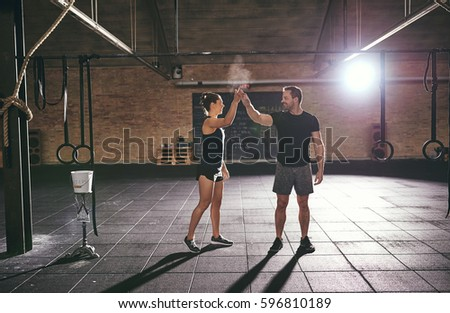 Young muscular sportsman and sportswoman exchanging high five in gym.