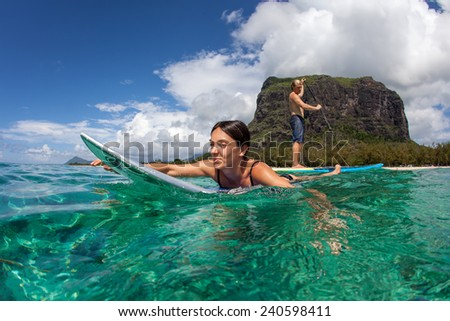 young muscular surfer with long white hair l watching the girl which surfing in the open ocean