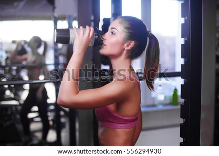 Young muscular woman drinking sports nutrition. #556294930