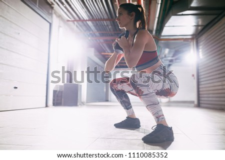Young muscular woman exercise goblet squat with kettlebell on hard training at the garage gym. #1110085352