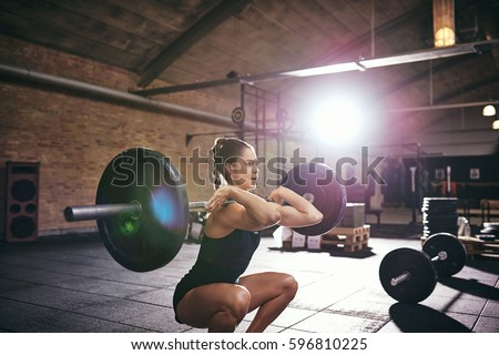 Young muscular woman in sportswear squatting with heavy barbell in spacious gym.