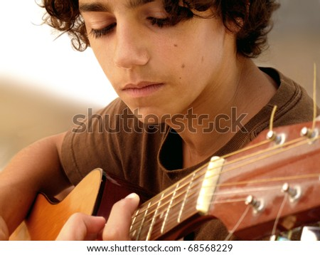 Young Musician Closeup: closeup shot of a 15 year old musician with acoustic guitar, very concentrated on his music. Selective focus.
