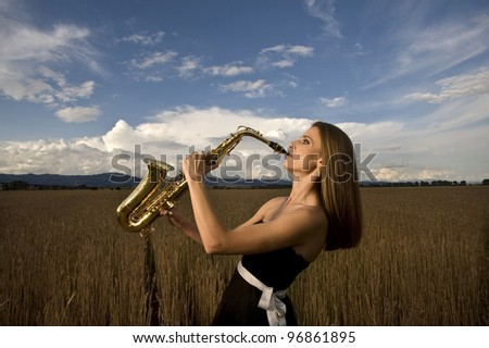 Young musician plays on saxophone in wheat field