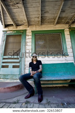 Young musician sitting in front of an abandoned house.