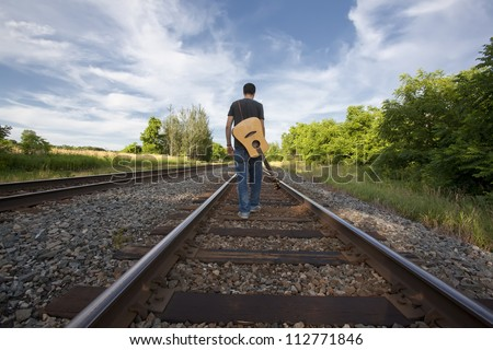 Young musician with guitar on back walking down center of train tracks.