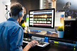 Young musician with headphones pressing keys of piano keyboard while sitting by computer monitor and working with sounds