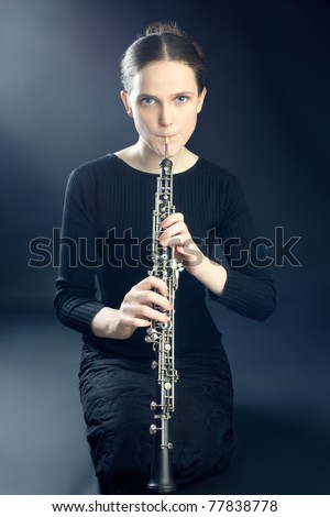 Young musician woman playing oboe. Oboist musical instrument play. It's instrument of classical symphony orchestra.