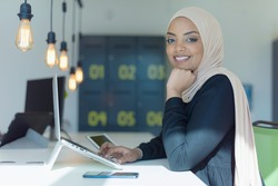 Young muslim African American business woman as a leader at work. Teamwork and multiethnic concept. Happy successful business leader working at her office, looking and smiling into camera.