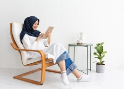 Young Muslim asian woman happy with tablet casual chair. Student is a journalist sit writing to be couching job concept for hijab girl Islam joyful internet on mobile smartphone technology. Ramadan