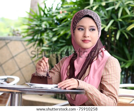 young muslim girl with cake on the table