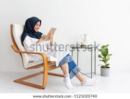 Young Muslim indonesian asian woman happy on tablet casual home chair. Malay Lady journalist sit texting concept hijab girl Islam business on phone smartphone video call online. Ramadan malaysian. Imagine de stoc ©