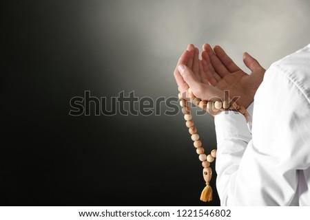 Young Muslim man with rosary beads praying on dark background, closeup Stok fotoğraf ©