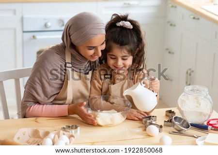 Young Muslim Mom Baking Together With Her Little Daughter In Kitchen. Cute Little Arab Girl Helping Mom To Prepare Dough, Adding Ingredients To Bowl, Islamic Family Having Fun While Cooking At Home
