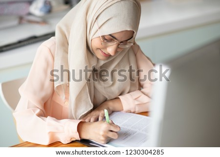 Young muslim  student writing and working in traditional clothes.