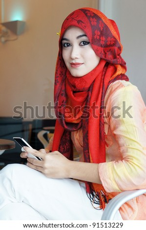 Young muslim stylish women writing text messaging at a cafe looking to camera