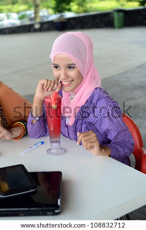 young muslim woman in head scarf drink at cafe