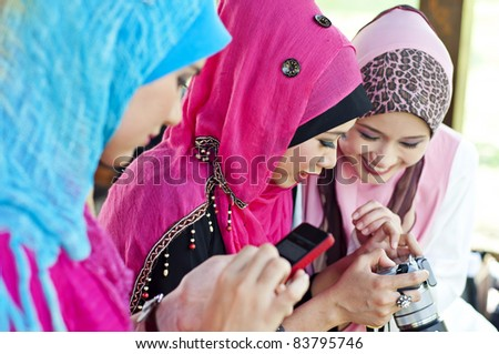 young muslim woman in head scarf using camera and handphone with friends