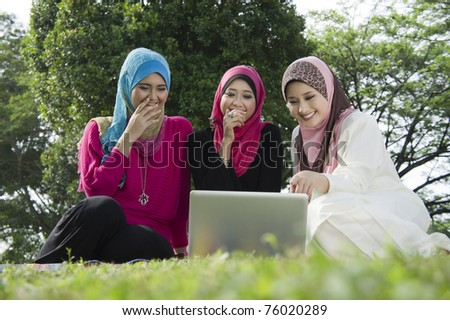 young muslim woman in hijab happy looking at laptop with friends