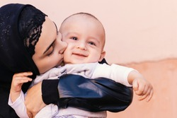 Young Muslim woman in hijab holding her 1-year-old baby boy, hugging and kissing. Happy Muslim mother in abaya clothing kiss and play with her little child. Cute family, middle-eastern mother and son