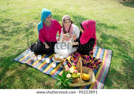 young muslim woman in hijab while relaxing and eating with friends in the park