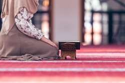Young muslim woman reading koran in mosque