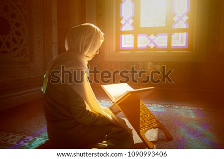 Young muslim woman reading Quran in the mosque and sunlight falling from the window #1090993406