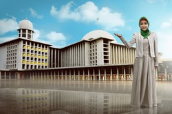 Young muslim woman show something with mosque background