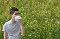 young myopic boy with asthma sneezes on a handkerchief because of allergy to grass on flowery field in Spring