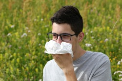 young myopic boy with glasses sneeze because of allergies to grass on flowery field in Spring