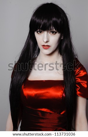Young mysterious fashion witch vampire with black hairs against the dark background - stock photo