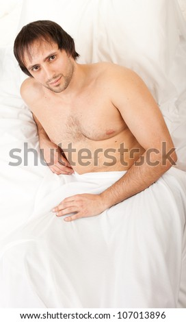 young naked man in bed with white sheets