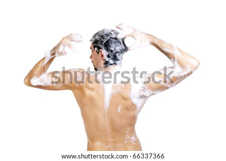 Young naked man taking a shower in foam with beautiful body isolated on white background
