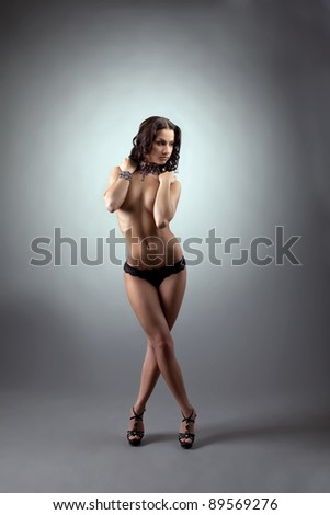 Young naked woman stand and close breast by hands