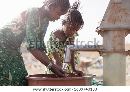 Young Native African Infant Saving Crisp Water for a lack of water symbol Stock photo ©