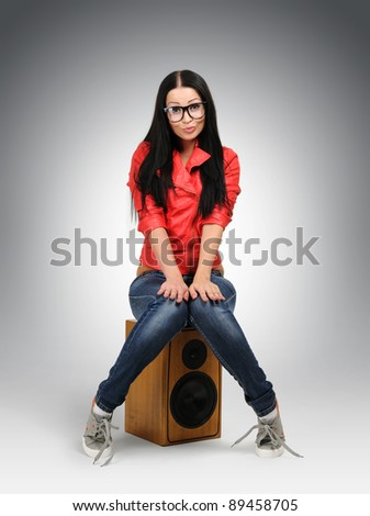 Young nerd fashion girl in large glasses with speaker