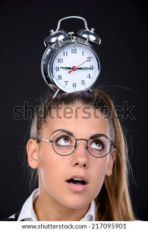 Young nerd woman crazy expression in glasses, holding an alarm clock on head on black background