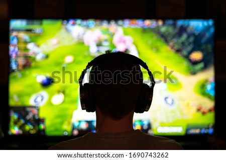 Young nerdy adolescent esport gamer playing and winning competitive internet MMORPG cyber championship in first person shooter strategy online video game wearing headphones on computer gaming rig