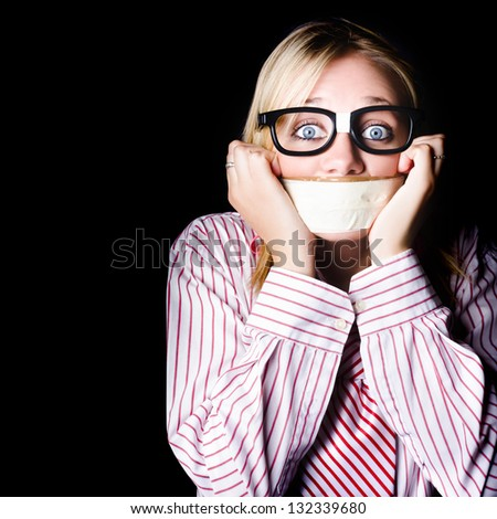 Young nerdy woman wearing eyeglasses, fearful with tape across her mouth