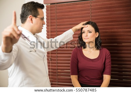 Young neurologist performing some neurological tests on a female patient in an office