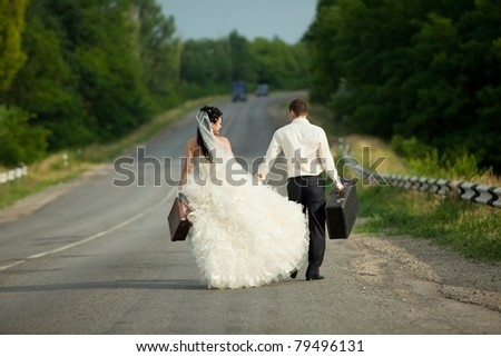 Young newlywed couple holding  suitcases of cash on countryside road