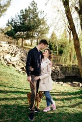 Young newlywed couple is kissing while holding their cocker spaniel puppy outdoors in autumn.