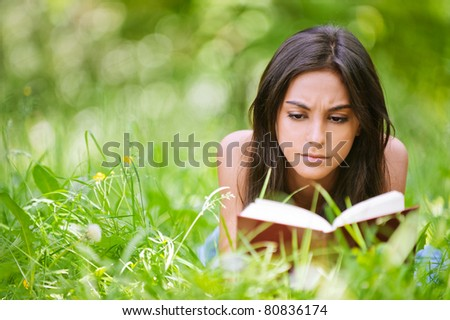 Young nice attentive woman lies on green grass and reads book against city park.