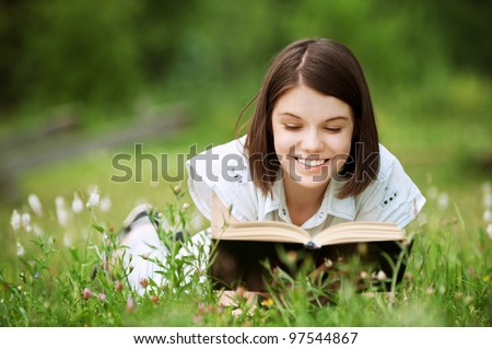 Young nice attentive woman lies on green grass and reads book at summer green park
