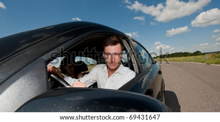 young nice businessman at the wheel in the car on the journey, a sunny day - stock photo