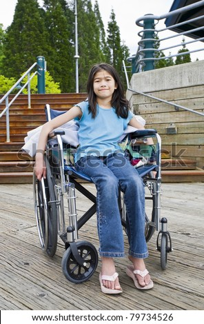 Young nine year old girl in wheelchair in front of stairs