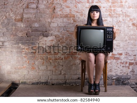 Young nude woman holding an old TV sitting in front of a brick wall.