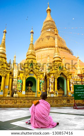 Young Nun praying at the Shwedagon Paya the most sacred buddhist temple in Myanmar Yangoon Myanmar