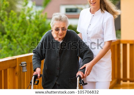Young nurse and female senior with walking frame, the caretaker helping her