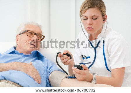 Young nurse checking the blood pressure of her old senior patient at hospital